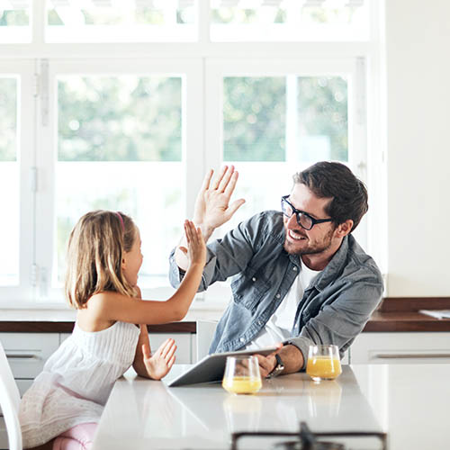 Father and daughter high-fiving in kitchen